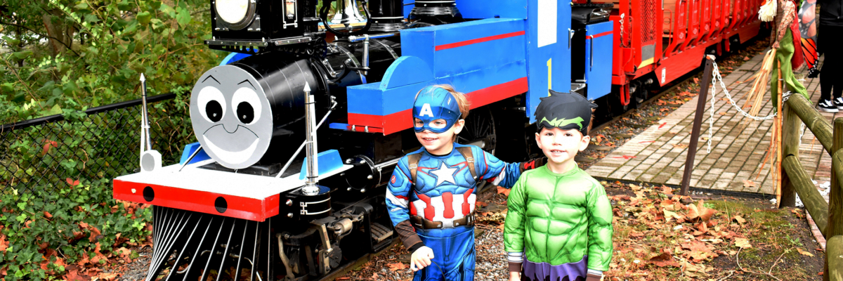 children in superhero costumes stand next to Thomas the train