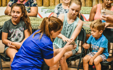 Zoo educator presents tenrec to young girl