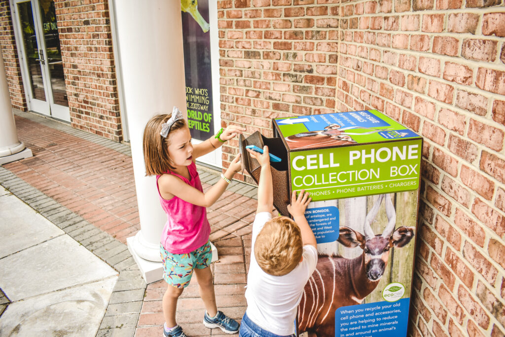 Small girl and boy opening a recycling box and putting in a cell phone