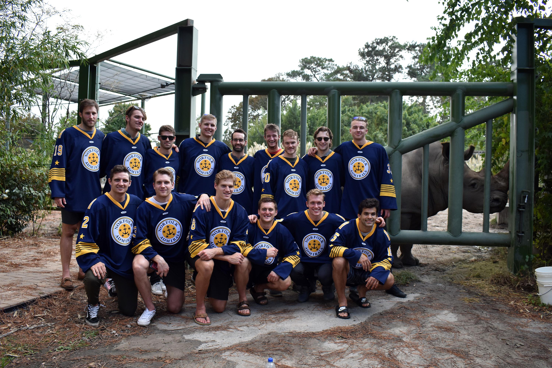 Norfolk Admirals hockey players in uniform pose with rhinos