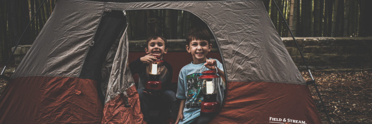 children holding lanterns inside tent
