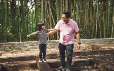 A dad and daughter play on balance beams