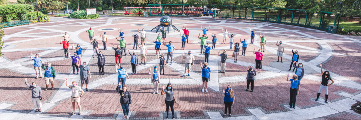 Virginia Zoo staff waiving while standing in the fountain plaza