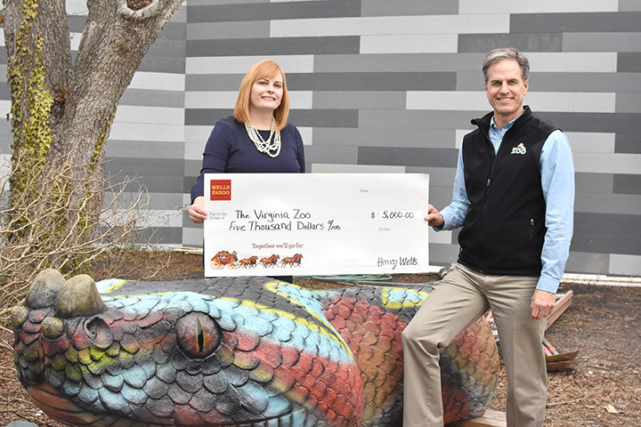 Woman and man standing with a large check donation