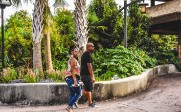 Female and male in masks walk past greenery and palm trees